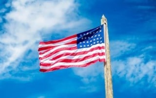 USA Flag Waving in a Beautiful Blue Sky